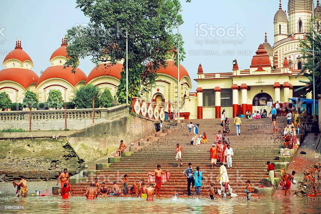 Many people bathing in water of river past temple stock photo