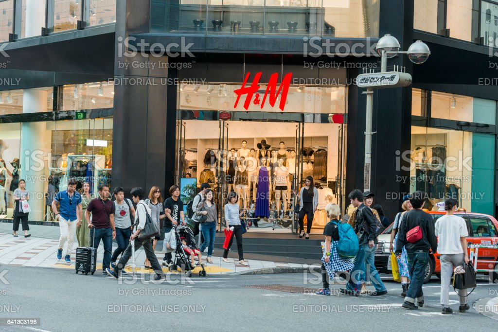 Many People Walk By H&M in Shibuya Shopping District Tokyo stock photo