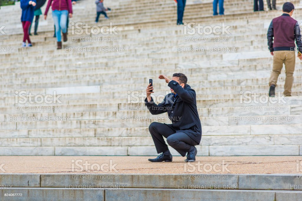 Many people walking around Thomas Jefferson Memorial stairs in winter with person taking selfie picture stock photo