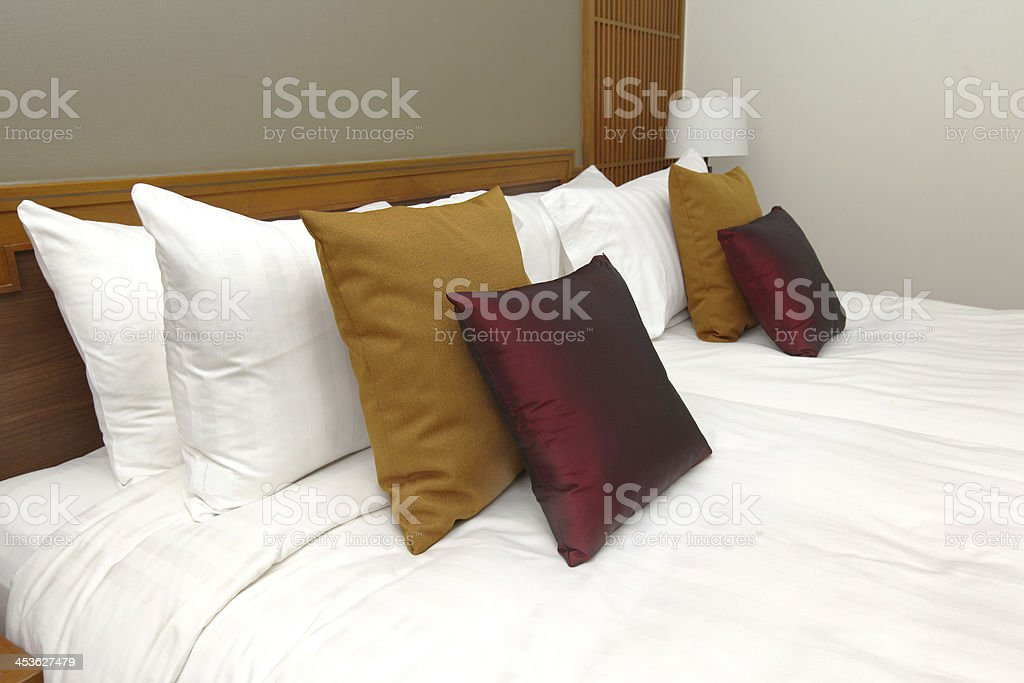 Many pillows on white bed room royalty-free stock photo