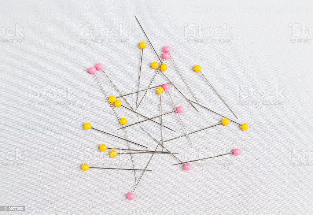 Many pins for needle work on white fabric stock photo