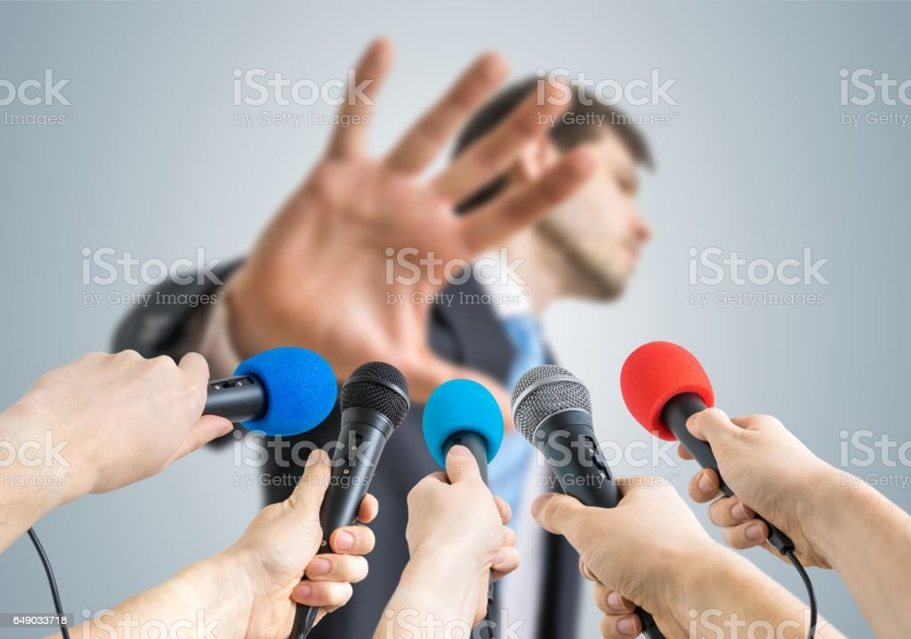 Many reporters are recording with microphones a politician who shows no comment gesture. stock photo
