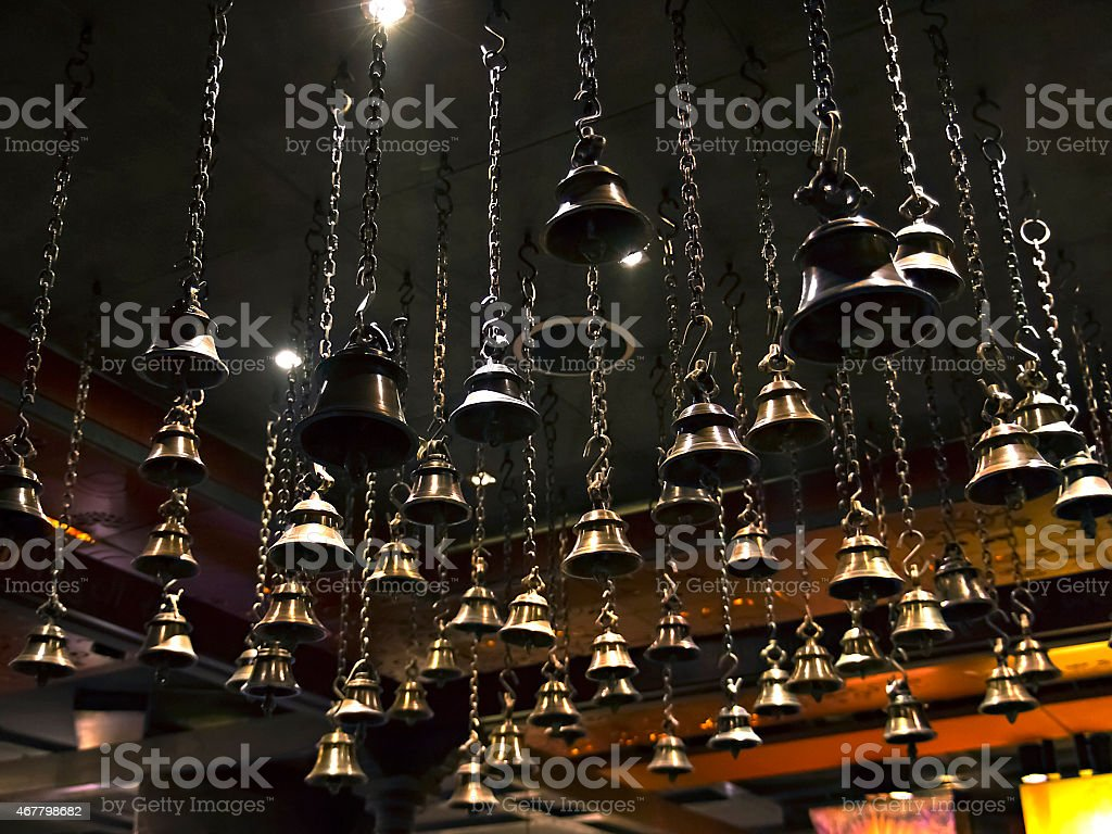 many ritual bells hanging on chains from the ceiling stock photo