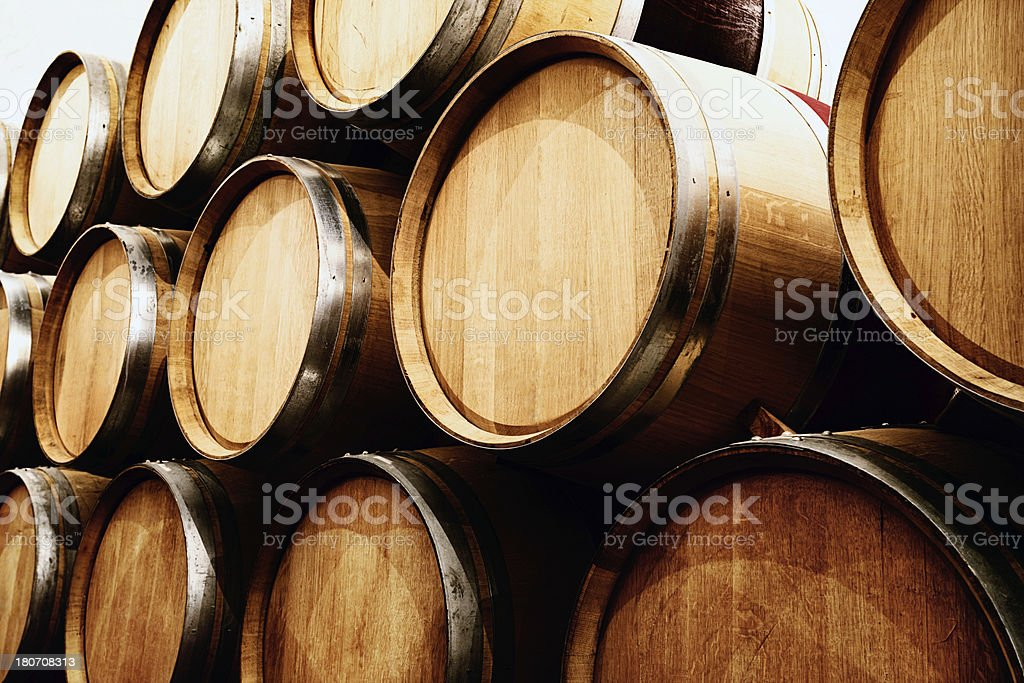 Many rows of stacked oak wine barrels in winery cellar royalty-free stock photo