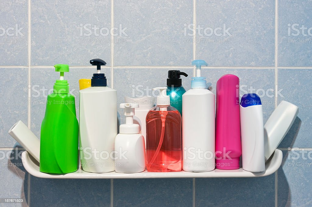 Many shampoo and soap bottles on a bathroom shelf. stock photo