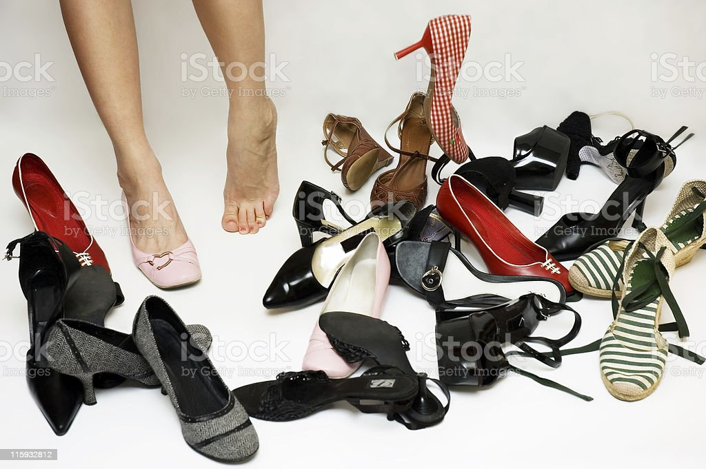 Female legs surrounded by many shoes