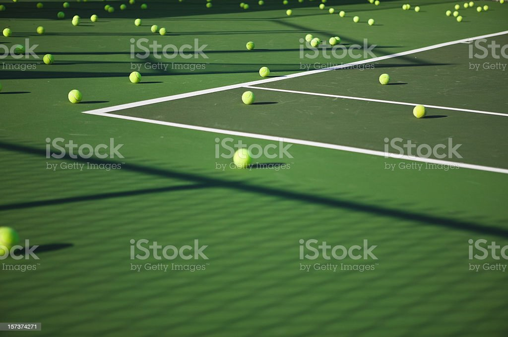 Many tennis balls laying on a green tennis court stock photo
