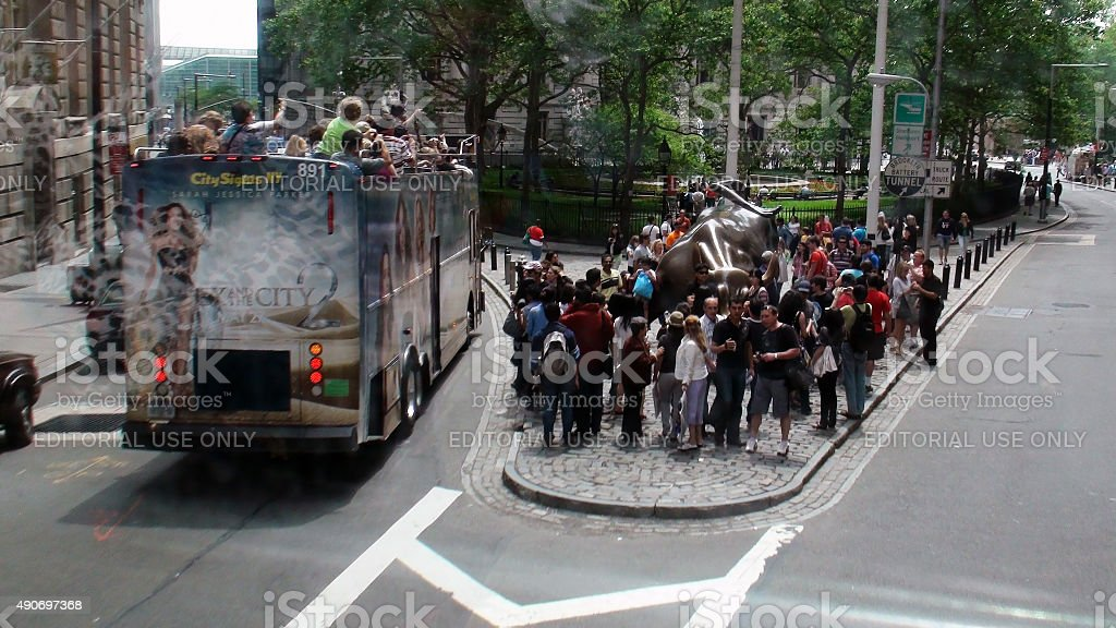 Many Tourist Checking Out Famous Wall Street Bull In NYC stock photo