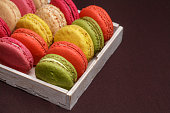 Many traditional french colorful macarons in a box, close-up