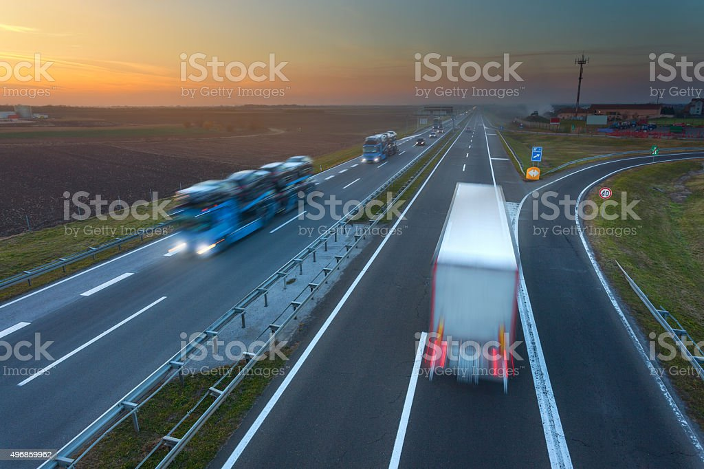 Many trucks in motion blur on the highway at sunset stock photo