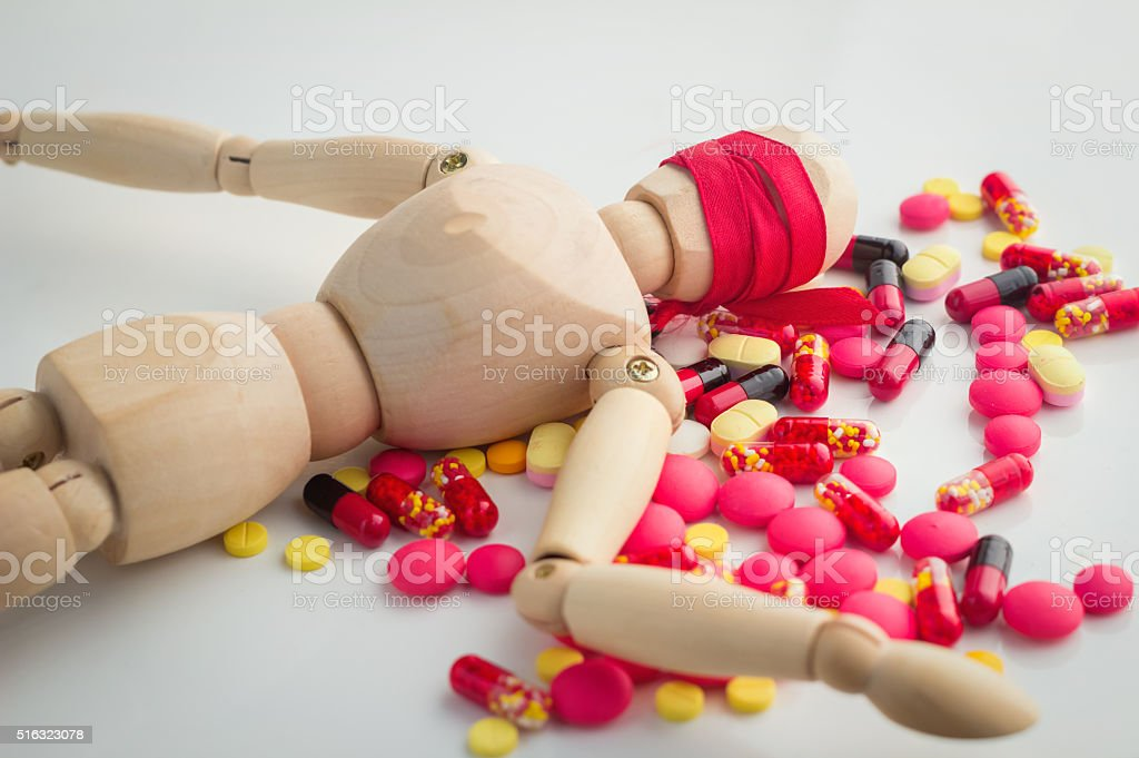 Many type of drugs pills and dead woodman figure.jpg stock photo