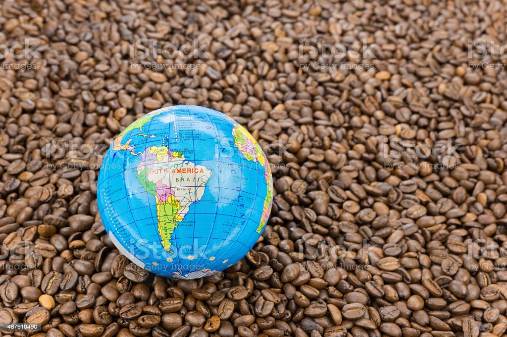 Many whole coffee beans with South America on globe stock photo
