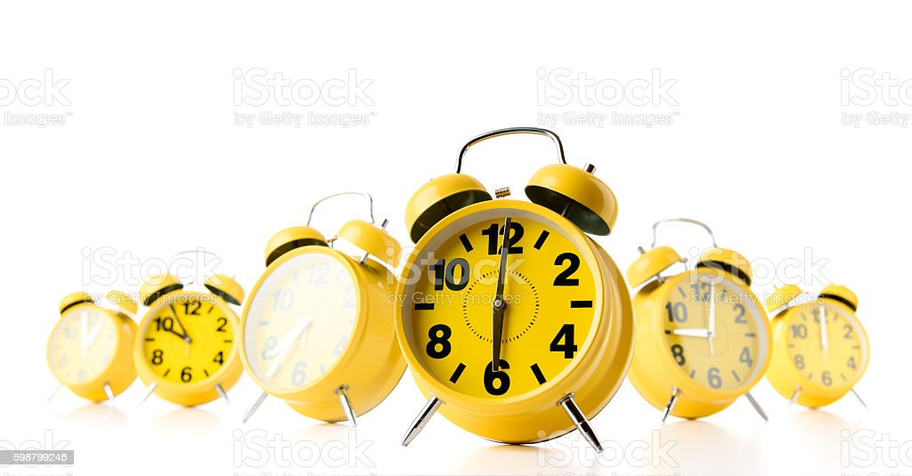 Many yellow alarm clock on white background. stock photo