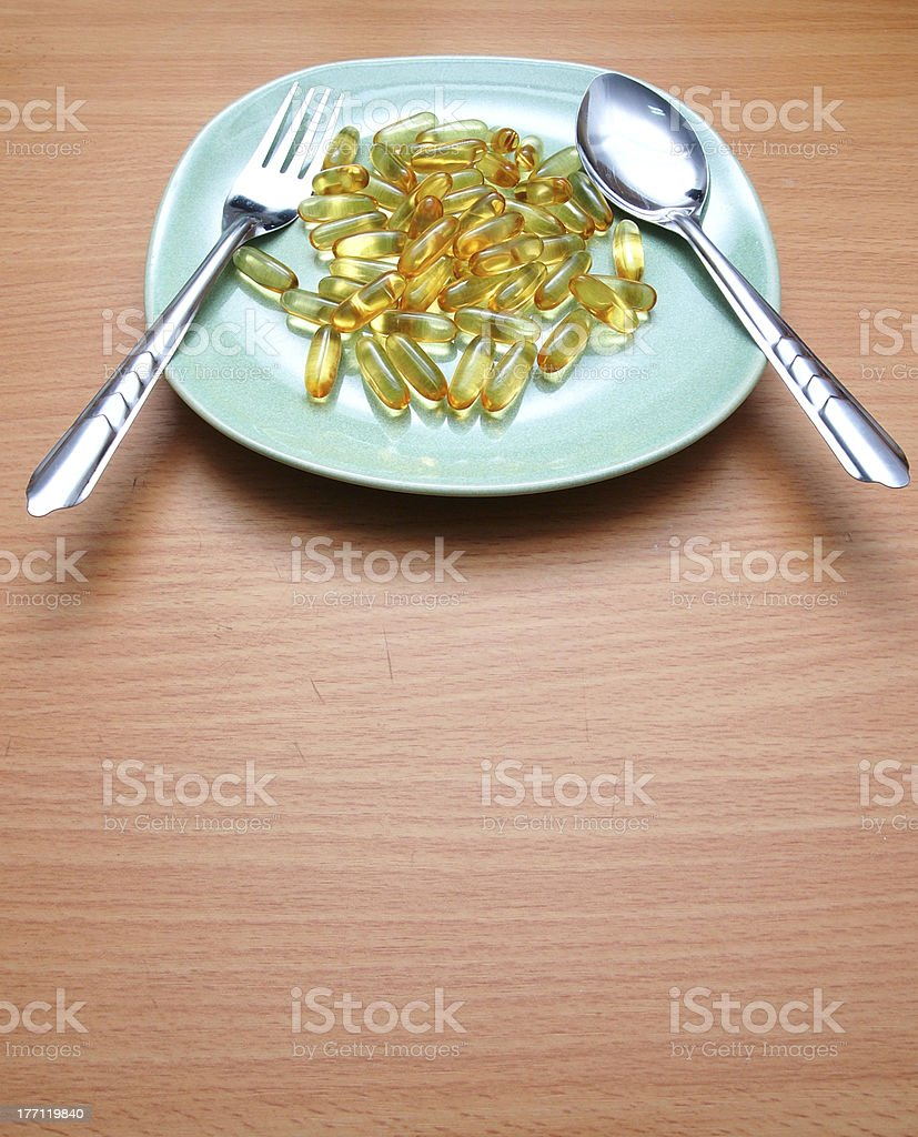 Many yellow vitamin on a plate royalty-free stock photo