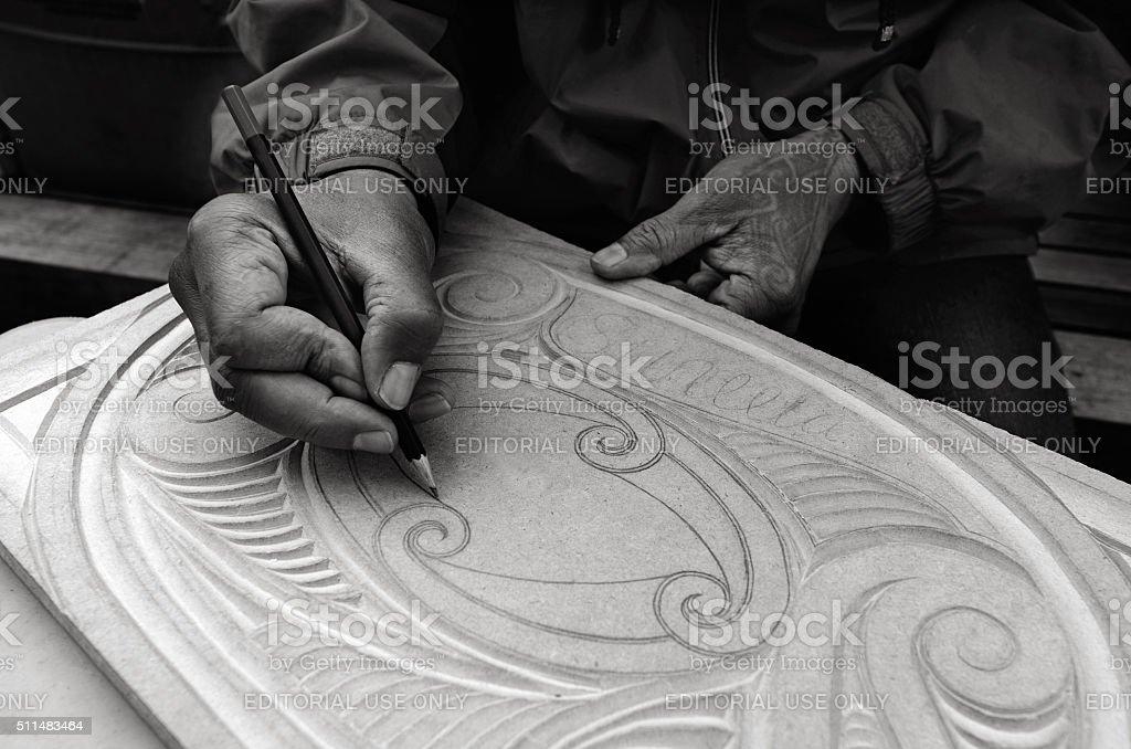 Maori man hands drawing patterns of Maori Wood carving stock photo