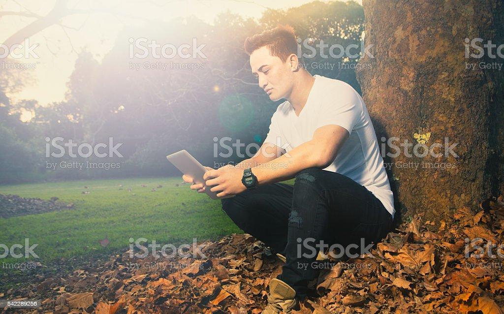 Maori man using Smart device stock photo