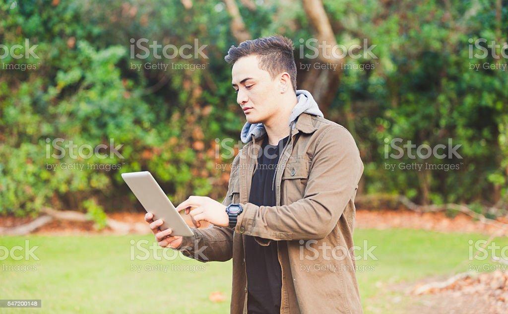 Maori Man using Tablet. stock photo