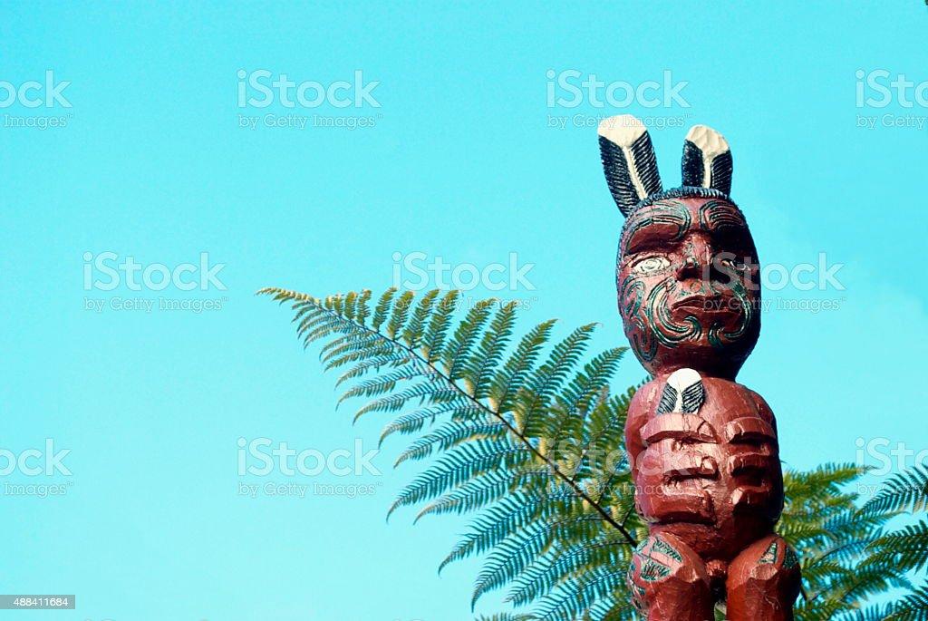 Maori Pou Figure with Ponga Fern and Sky stock photo