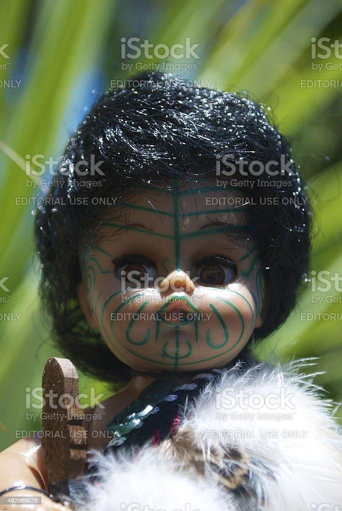 Maori Souvenir Doll with New Zealand Flax Background stock photo
