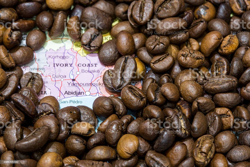Map of Ivory Coast under a background of coffee beans stock photo