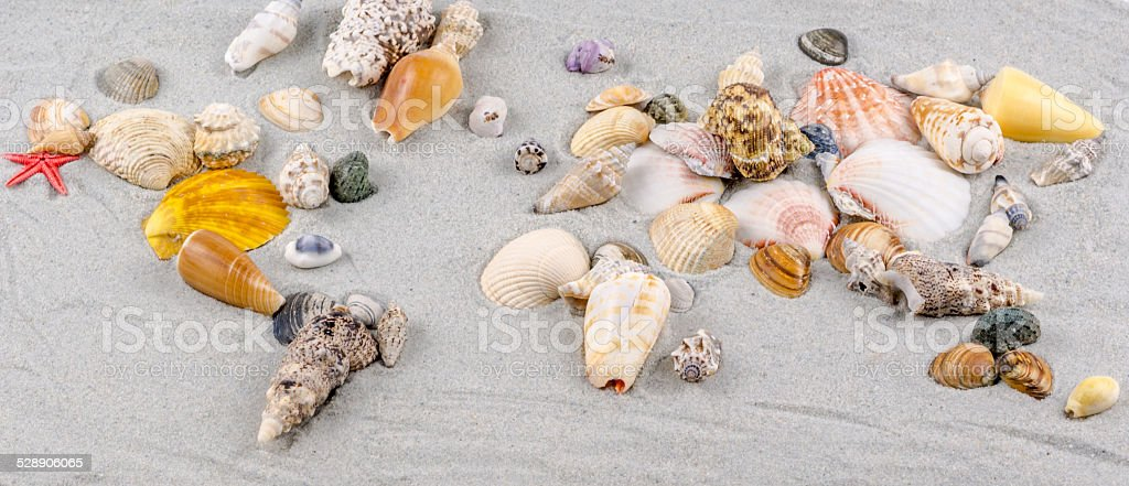 map of the world made of shells on sand stock photo