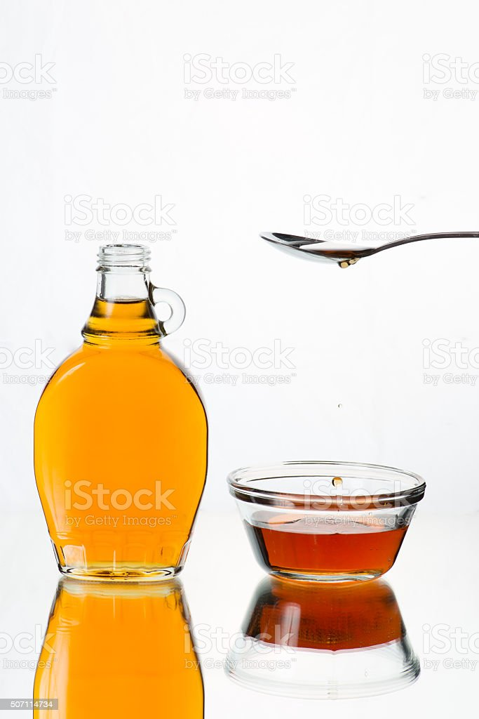 Maple Syrup dripping from a spoon stock photo