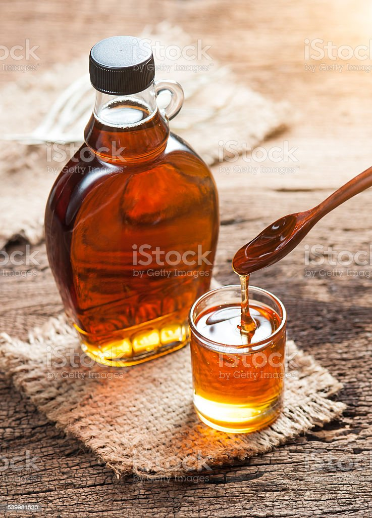 maple syrup in glass bottle on wooden table stock photo