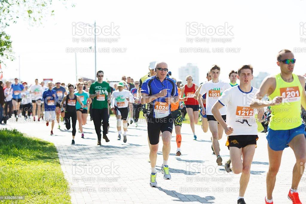 Marathon athletes running on street. stock photo