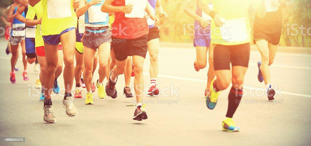 Marathon runner running on city road stock photo