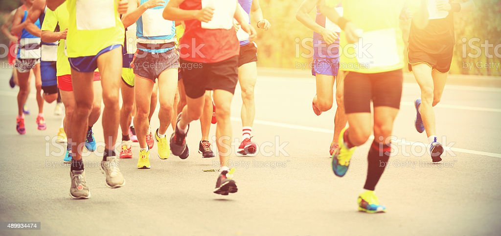 Marathon runner running on city road stock photo