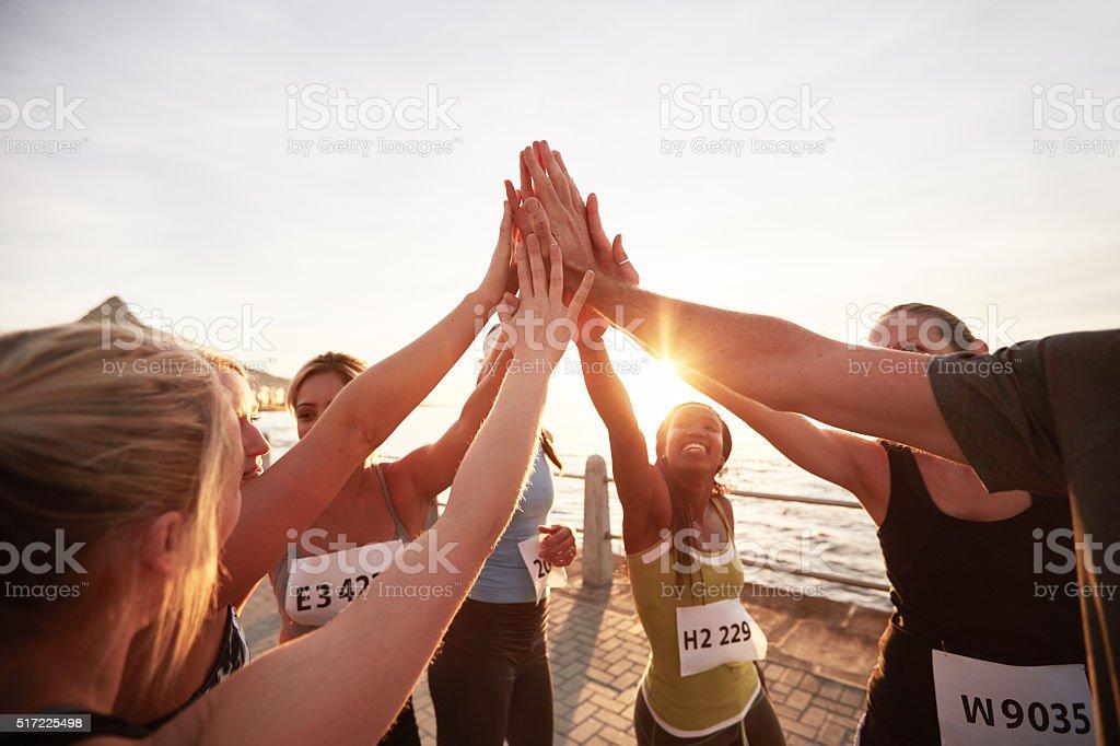 Marathon runners giving high five stock photo