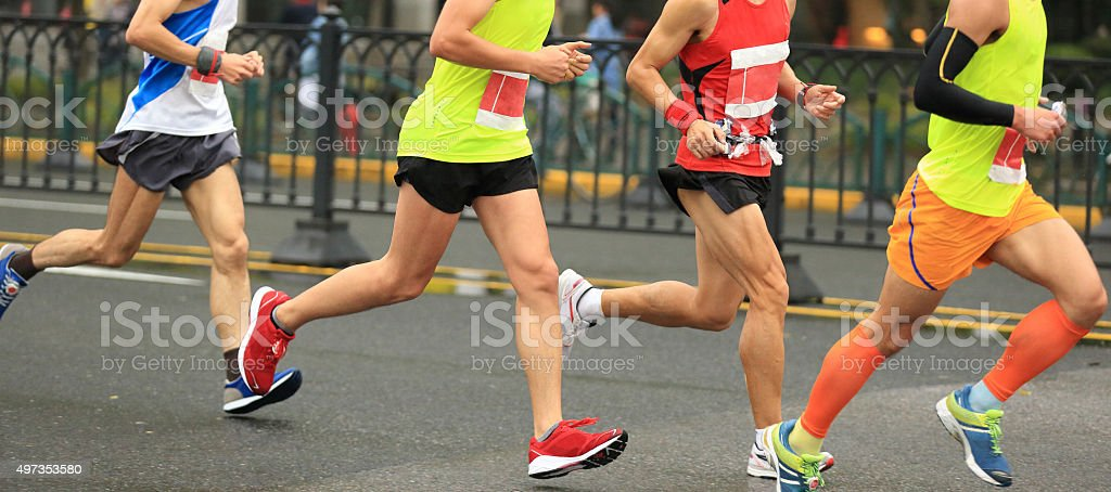 marathon runners running on city road stock photo