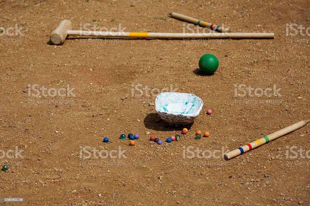 Marble balls on sand background. Croquet mallet. Playing children equipment. stock photo