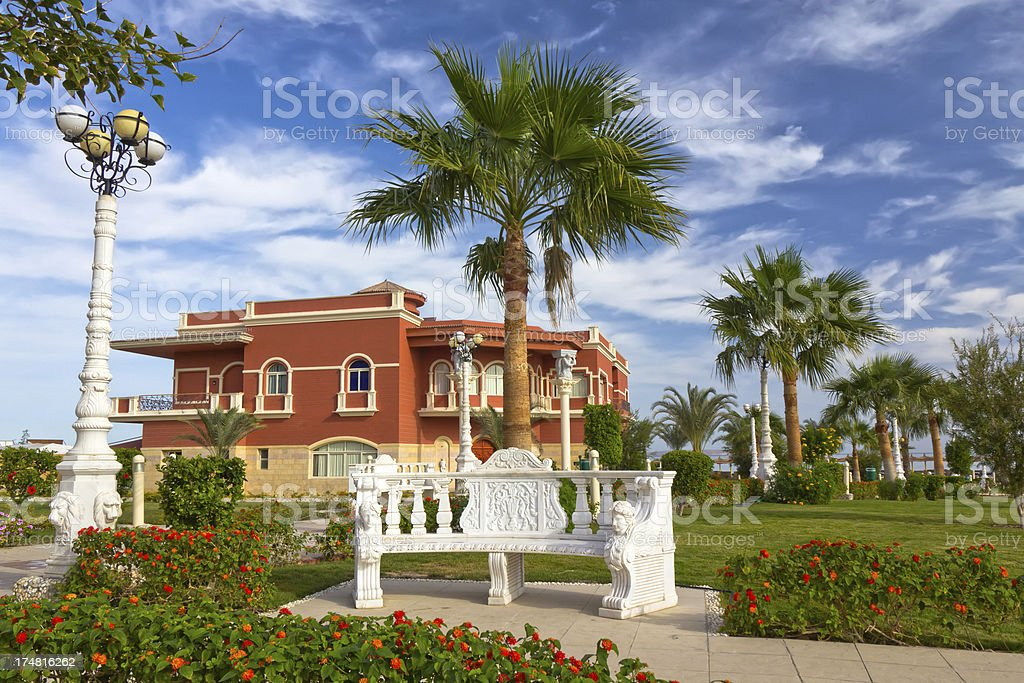 Marble bench and Arabian rsidential house in a tropical park royalty-free stock photo