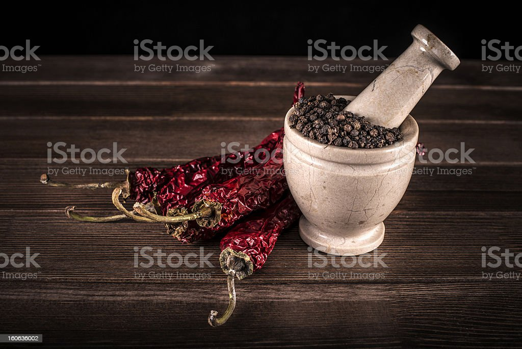 marble mortar with spices and black red hot pepper royalty-free stock photo