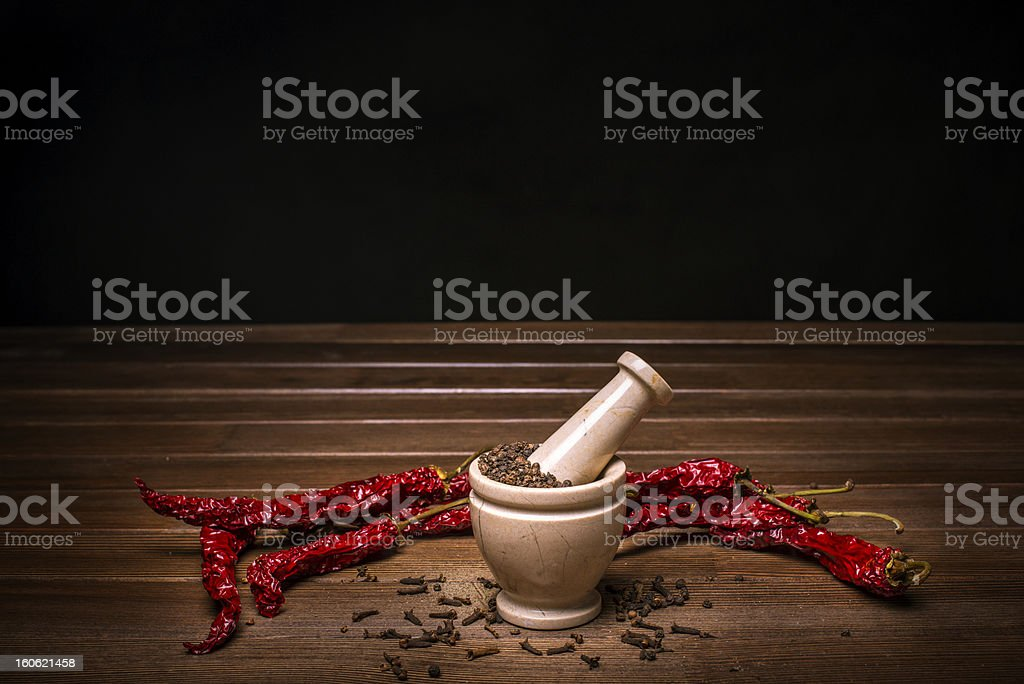 marble mortar with spices carnation and black red hot pepper royalty-free stock photo
