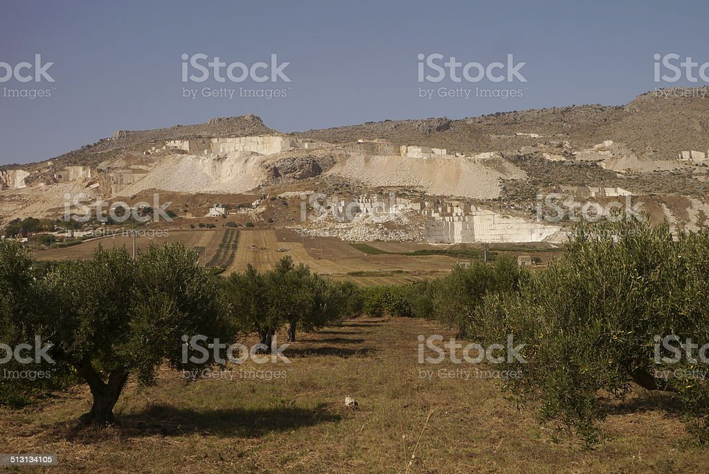 Marble quarry behind olive grove stock photo