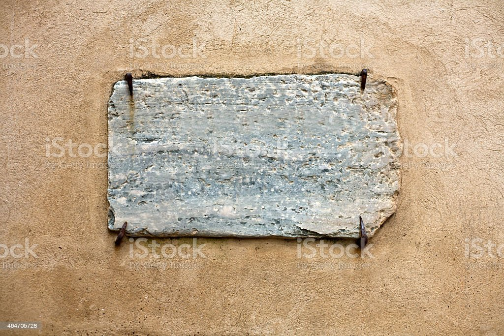 Marble signboard hold by rusty nails stock photo