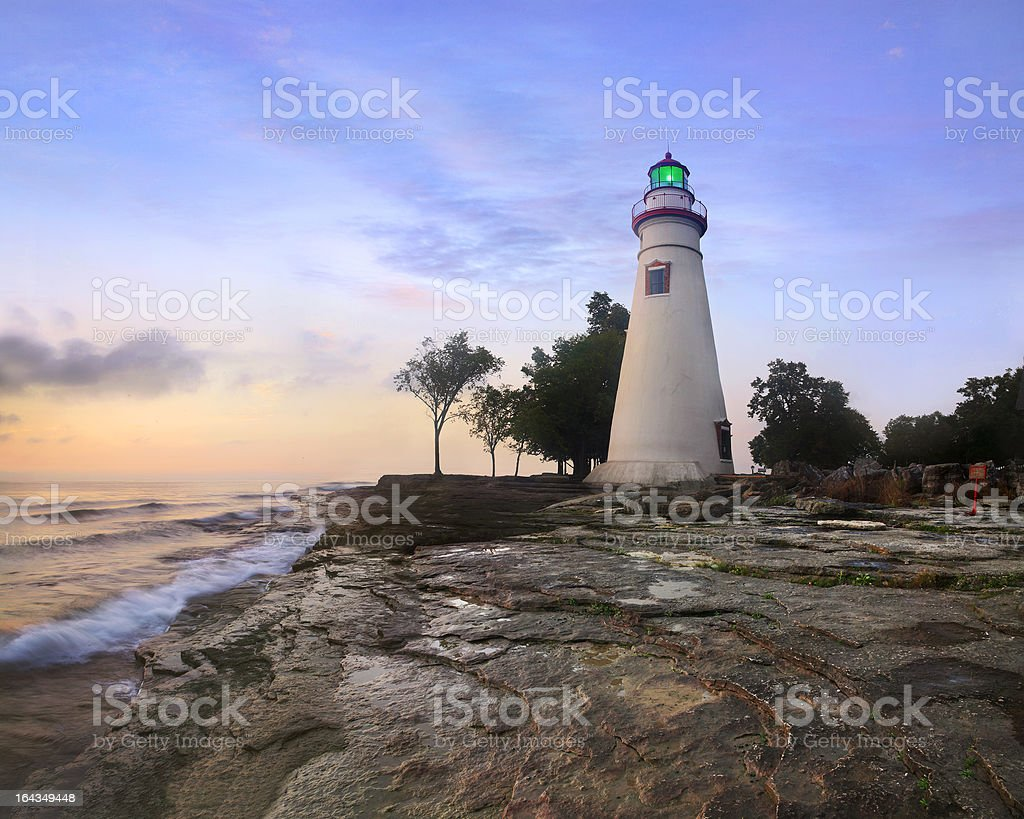 Marblehead Lighthouse and waves against rocks at sunrise royalty-free stock photo