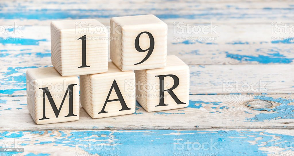March 19th. Wooden cubes with date of 19 March on old blue wooden background. stock photo