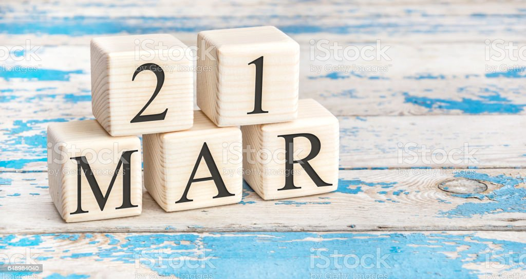 March 21st. Wooden cubes with date of 21 March on old blue wooden background. stock photo