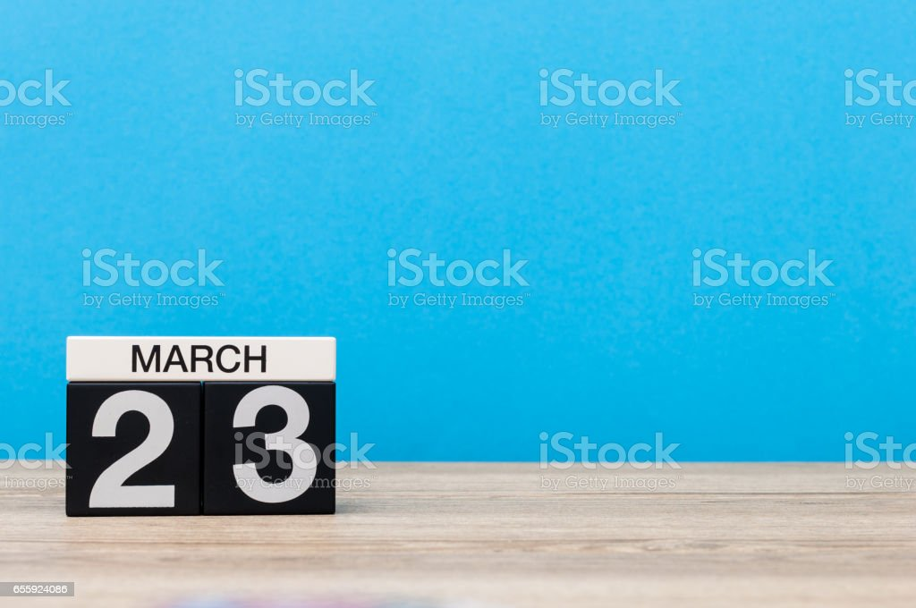 March 23rd. Day 23 of month, calendar on table with blue background. Spring time, empty space for text stock photo