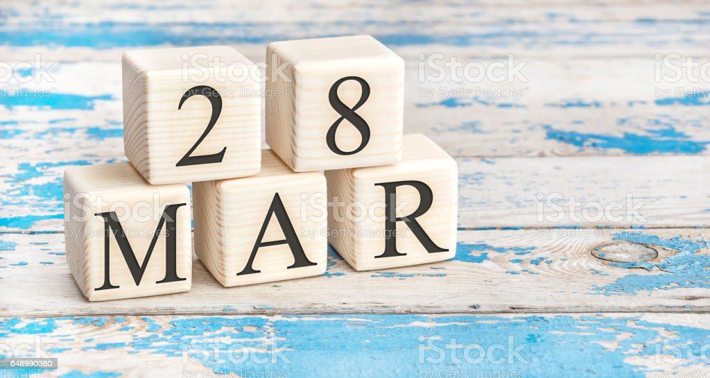 March 28th. Wooden cubes with date of 28 March on old blue wooden background. stock photo
