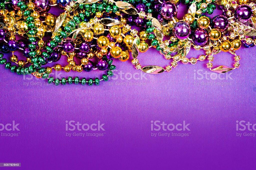 Mardi Gras background.  Purple, gold, green, beads. stock photo