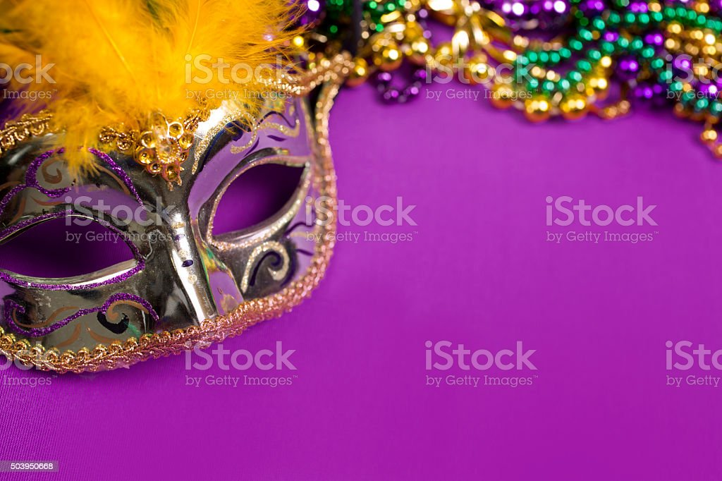 Mardi Gras background. Colorful, feathered gold masquerade mask with...