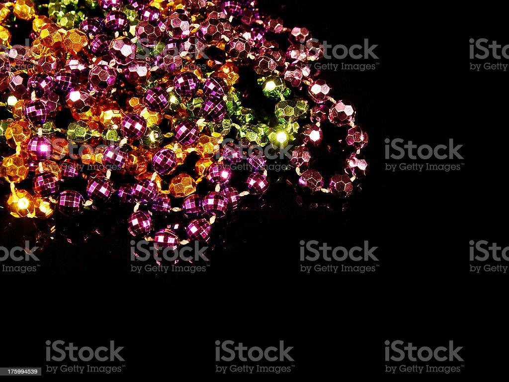 Mardi Gras beads isolated on black acrylic royalty-free stock photo