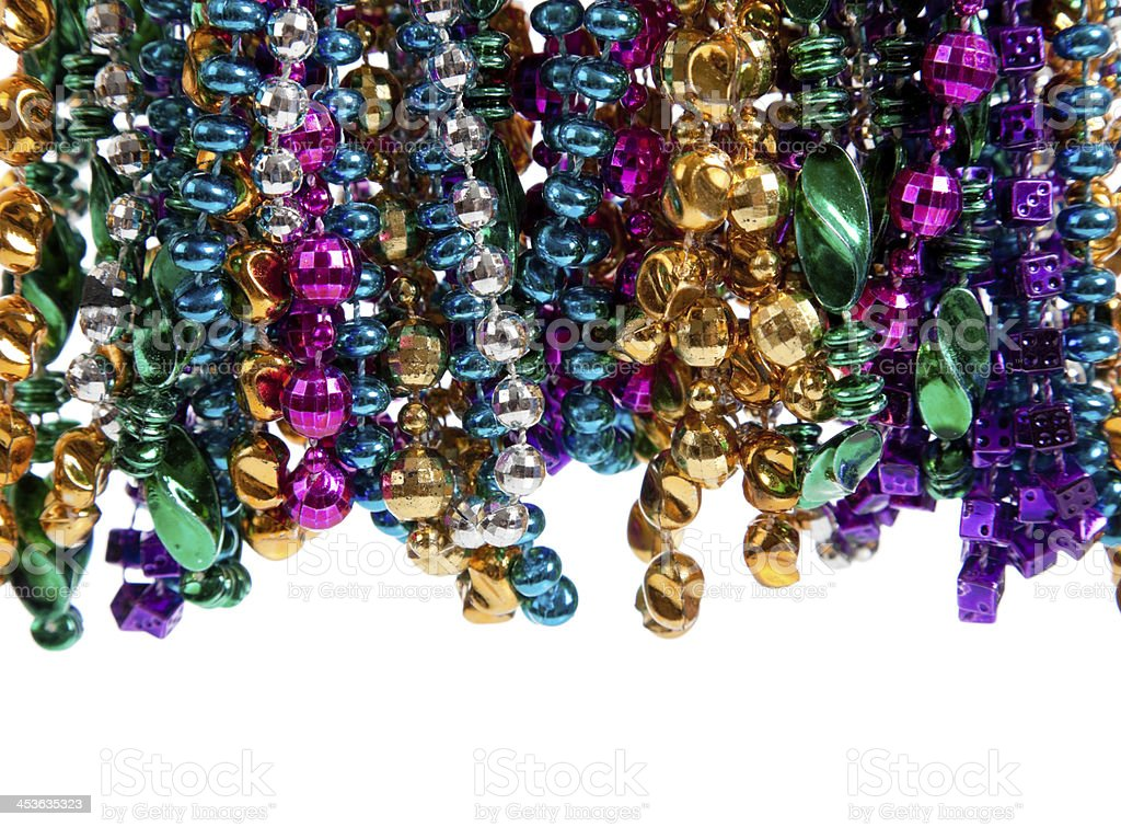 Mardi gras beads on white with copy space stock photo