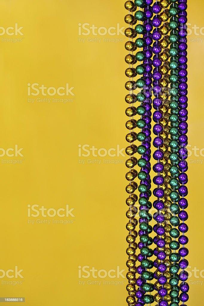 Mardi Gras Beads on Yellow royalty-free stock photo