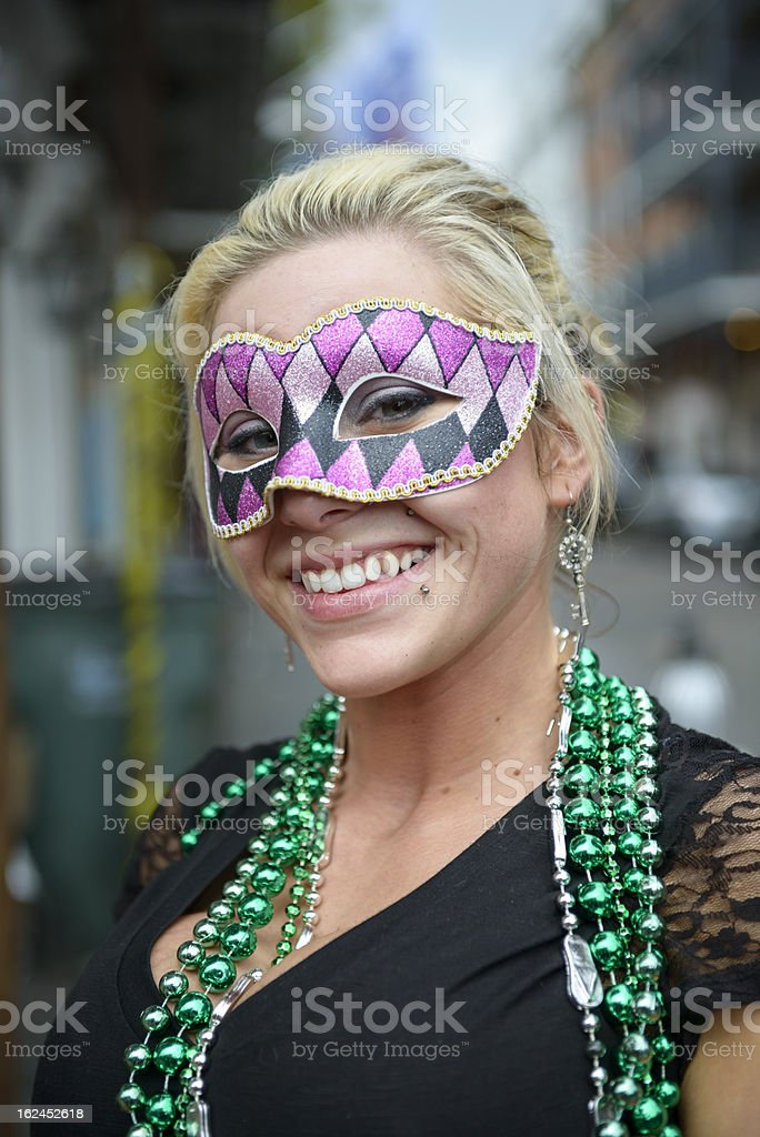 Mardi Gras girl with green beads and carnival mask stock photo