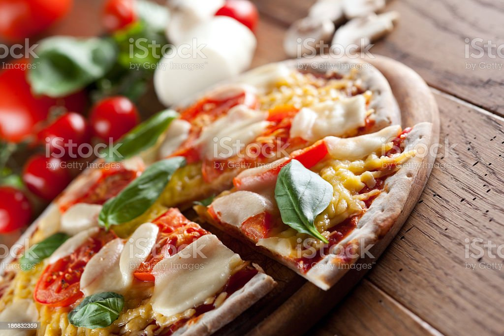 A margharita pizza with basil leaves, tomatoes and cheese stock photo